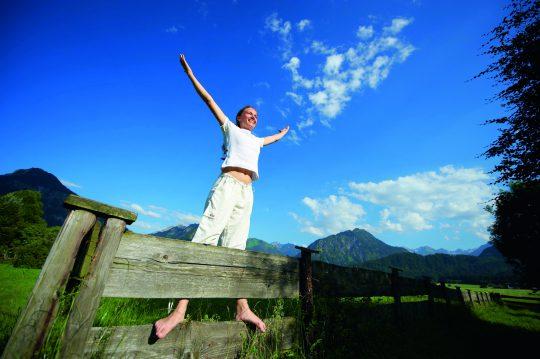 Frau steht auf Zaun und genießt den Sommer in Schüle's Gesundheitsresort & Spa