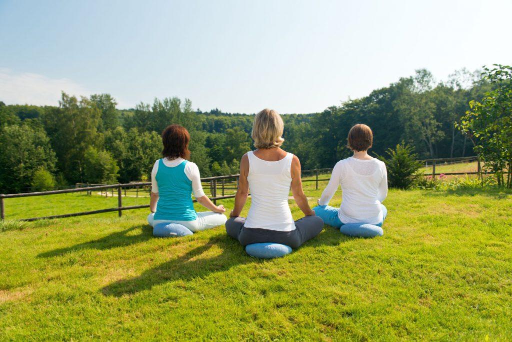 Drei Frauen entspannen beim Yoga im Hotel Heinz