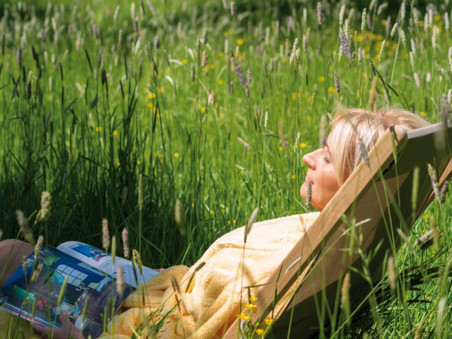 Frau entspannt bei Buch im Hotel Sonnengut