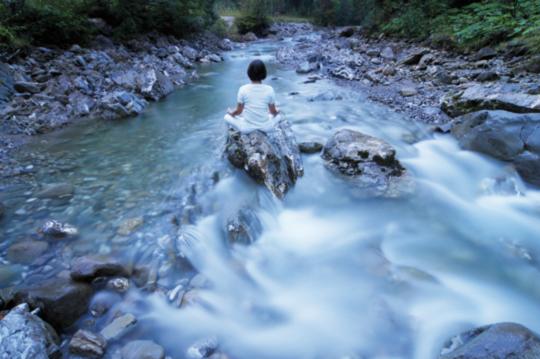 Entschleunigung im HUBERTUS Alpin Lodge & Spa: Frau macht Yoga im Fluss und entspannt dabei