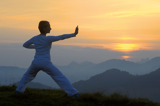 Frau macht Yoga in der Natur im Hubertus Alpin Lodge & SPa
