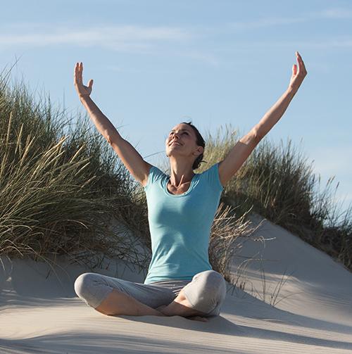 Frau entspannt bei gutem Wetter beim Yoga am Strand von Norderney, Nordsee; Bild von den Wellness-Hotels & Resorts