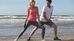 Frau und Mann machen gemeinsam Sport im Sommer am Meer